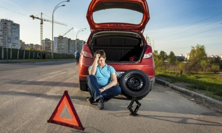 Portrait of depressed man leaning against broken car