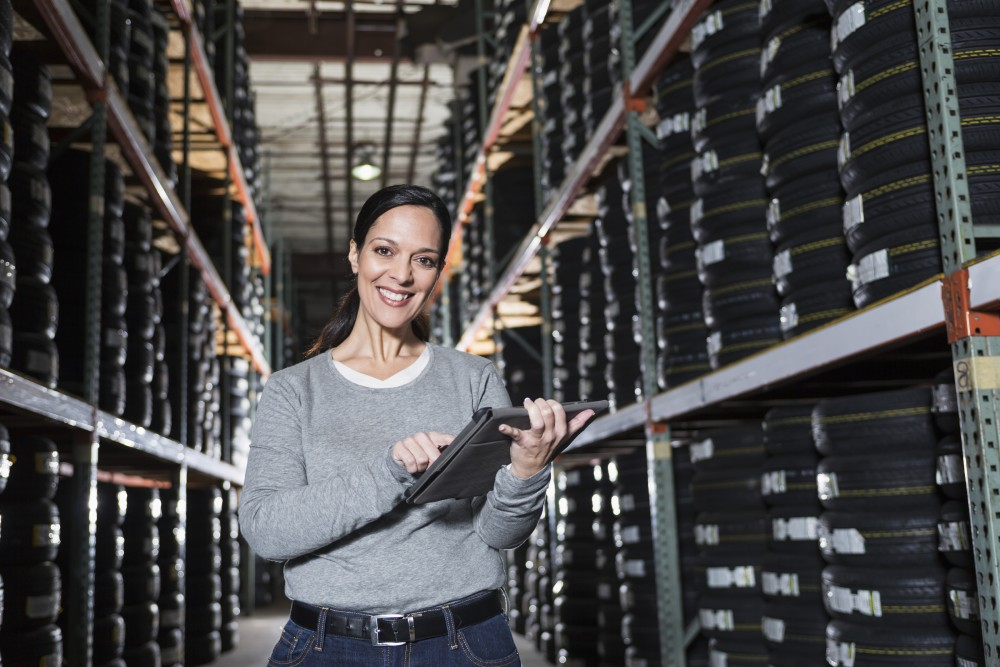 Hispanic woman (30s) working in warehouse with shelves of tires, taking inventory on digital tablet.