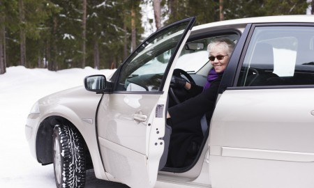 Stylish elderly woman sitting in her car.