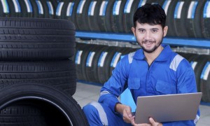 Young mechanic checking tires while holding laptop computer in the tire store
