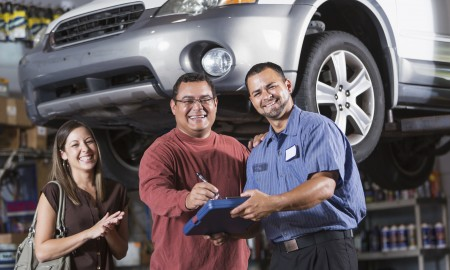 Couple with mechanic in auto repair shop.  All are Hispanic.  Main focus on men (30s, 40s).