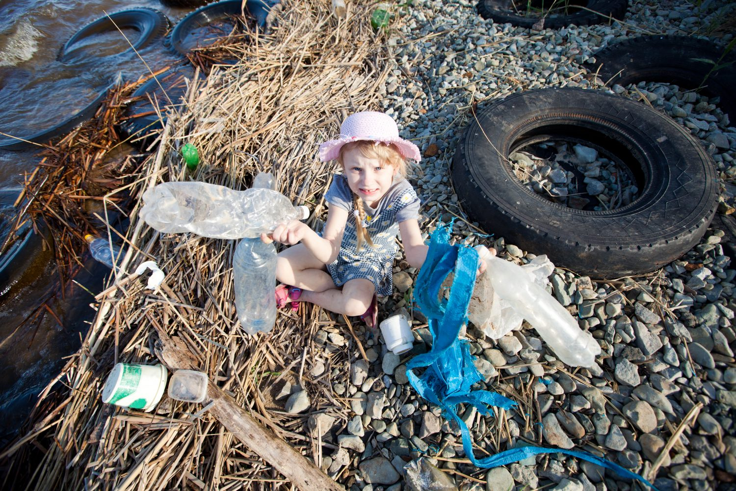 small girl collecting rubbish near the river