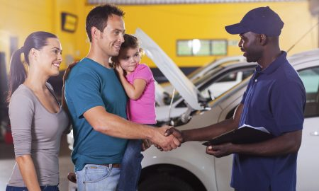 friendly auto mechanic handshaking with family inside workshop