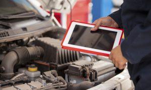 Closeup of a mechanic using a tablet computer next to an open hood in an auto shop