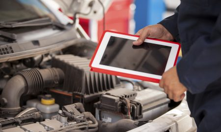 Closeup of a mechanic using a tablet computer next to an open hood in an auto shop