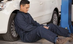 Young mechanic taking a break and social networking at an auto shop