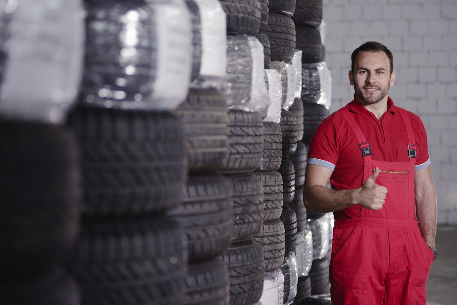 in car worshop mechanic with old tires
