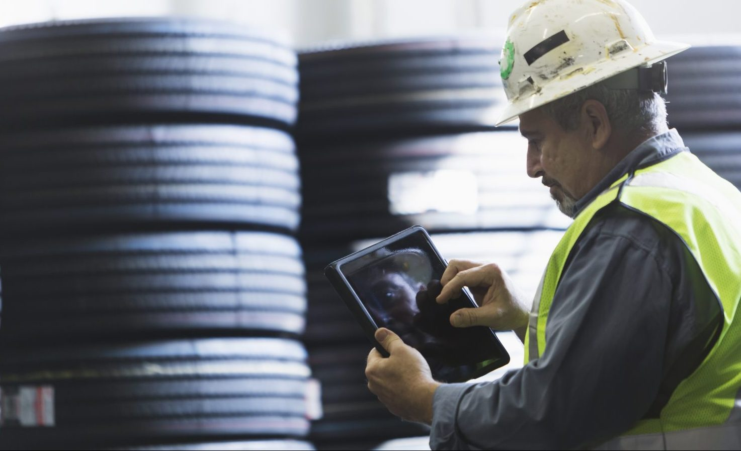 A mature man, in his 50s, wearing a white hardhat and yellow safety vest, is working in a warehouse full of truck tires.  He is using a digital tablet to take inventory of the stacks of product.