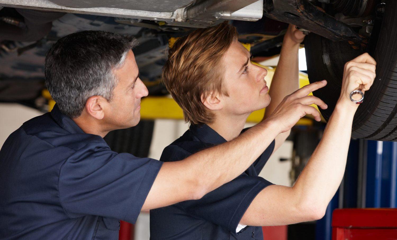 Mechanics at work under car in workshop
