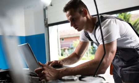 Repairman using laptop for diagnostic car