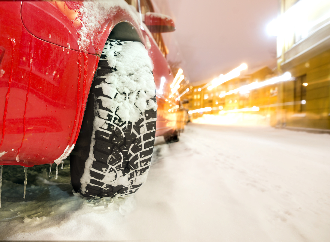 Studded tyre of red car on street in winter evening