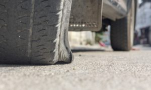 burst car tire on street.