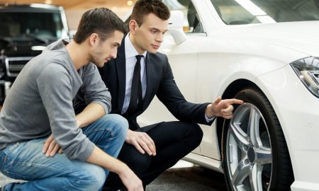 Young car salesman showing the advantages of the car to the customer