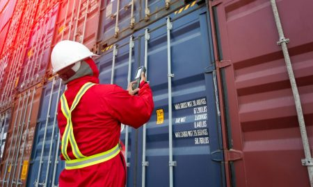 Foreman control loading Containers box from Cargo freight ship,Freight shipping containers at the docks,Large container shipping at shipping yard main transportation of cargo container shipping.