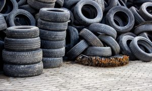 Waste of used car tires in the tire repair shop yard with a copy space.