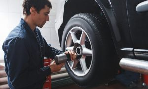 Mechanic changing car wheel in auto repair shop. Closeup of serviceman with tools working near castor of automobile in garage.