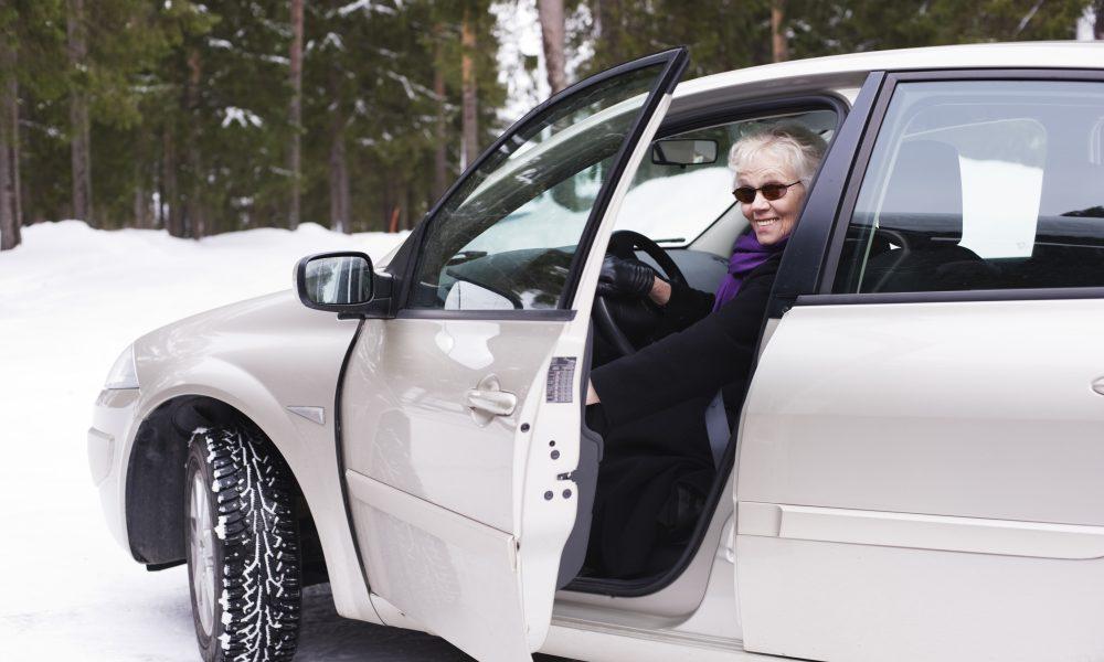 Stylish elderly woman sitting in her car.
